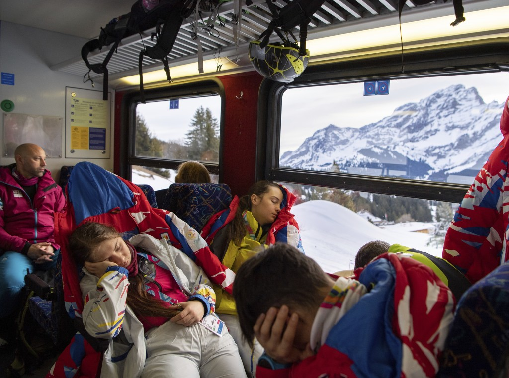 In this photo from the OIS, athletes from Romania grab every opportunity for extra rest on the early train to the Ski Mountaineering competition at Vi...