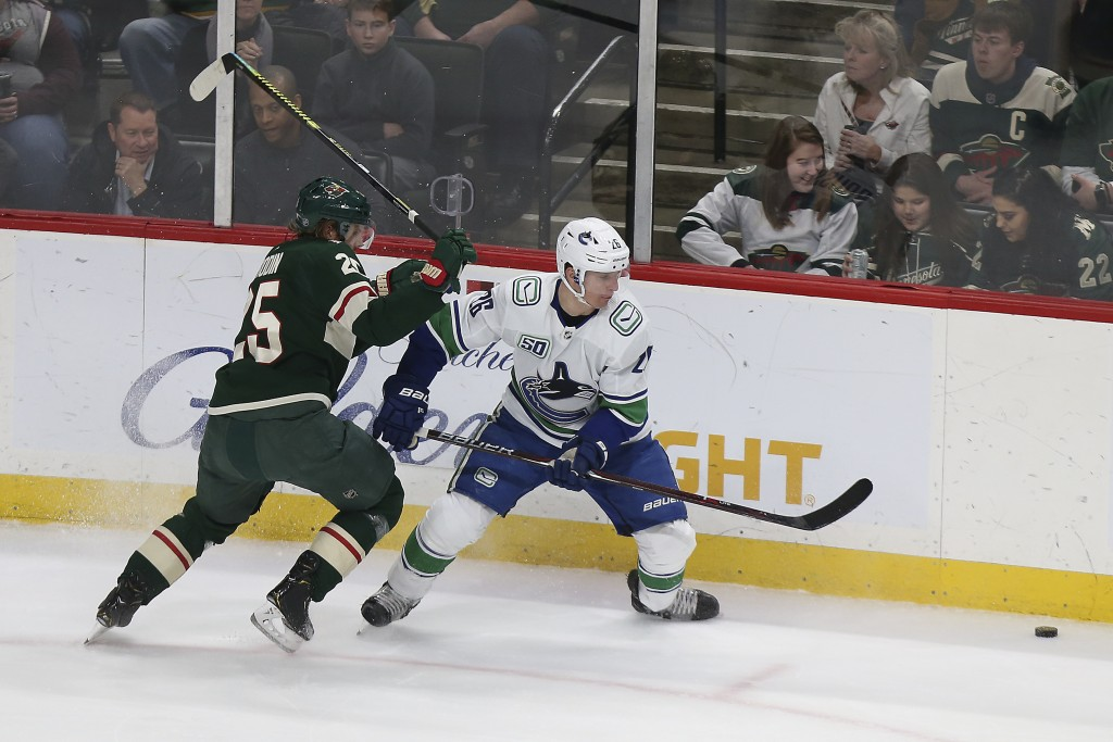 Minnesota Wild's Jonas Brodin, left, and Vancouver Canucks' Antoine Roussel, of France, go after the puck in the first period of an NHL hockey game Su...