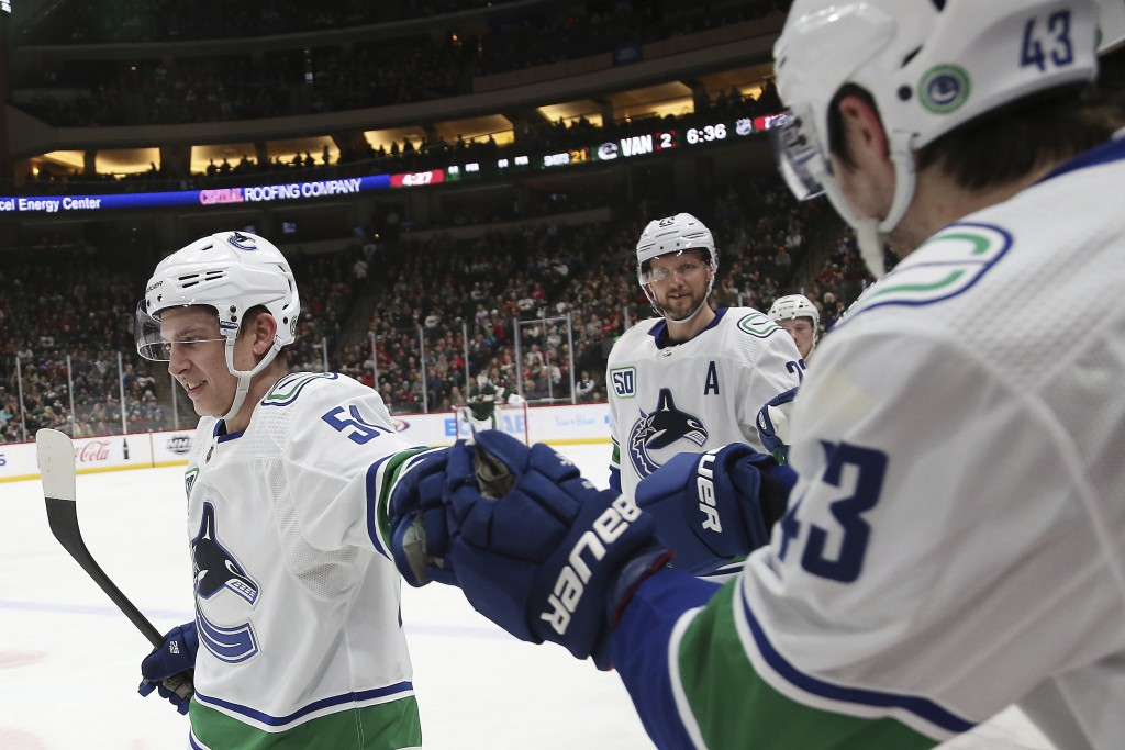 Vancouver Canucks' Troy Stecher, left, high-fives teammate Quinn Hughes after scoring a goal against the Minnesota Wild in the second period of an NHL...