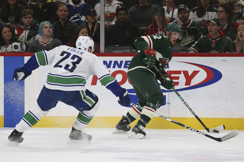 Minnesota Wild's Eric Staal, right, controls the puck against Vancouver Canucks' Alexander Edler, of Sweden, in the second period of an NHL hockey gam...