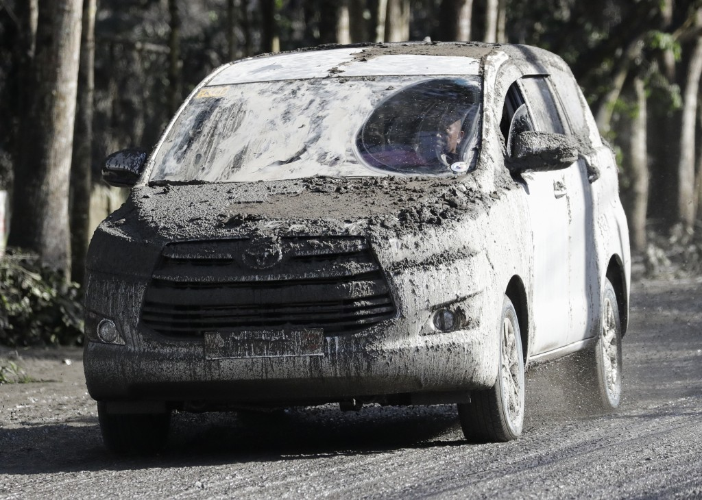 In this Monday, Jan. 13, 2020, photo, an ash-covered vehicle drives down a muddy road as Taal volcano continues to erupt in Tagaytay, Cavite province,...