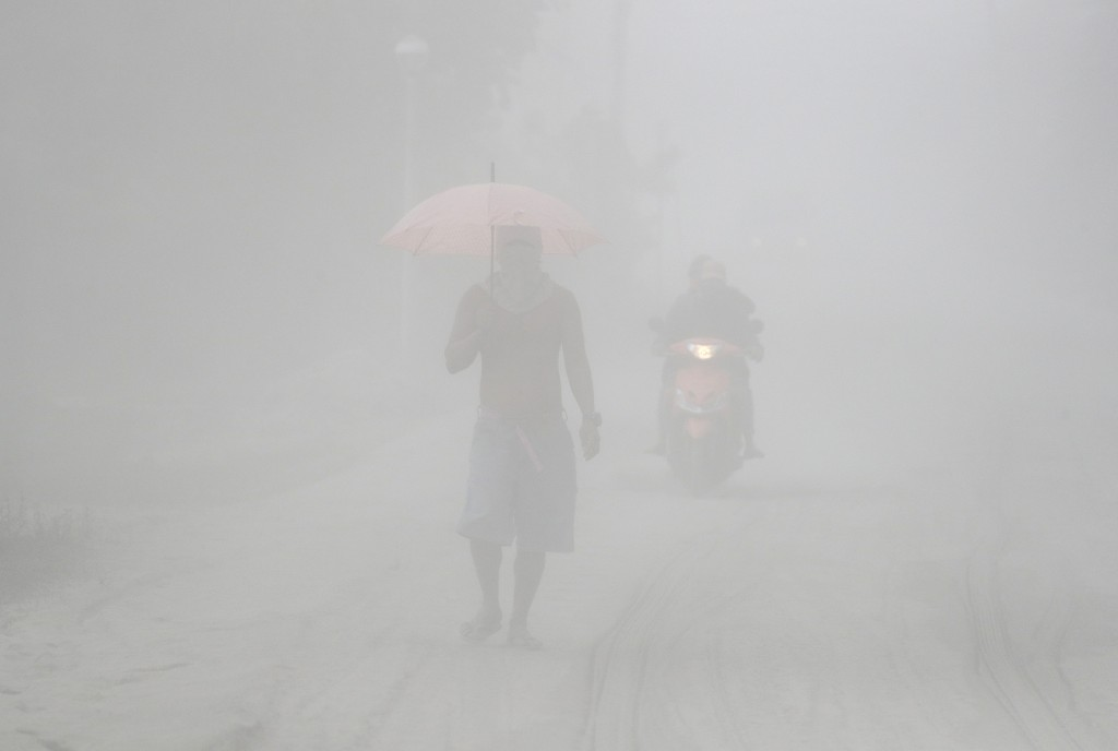 In this Monday, Jan. 13, 2020, photo, a man walks through a cloud of volcanic ash as he evacuates to safer grounds as Taal volcano in Lemery, Batangas...