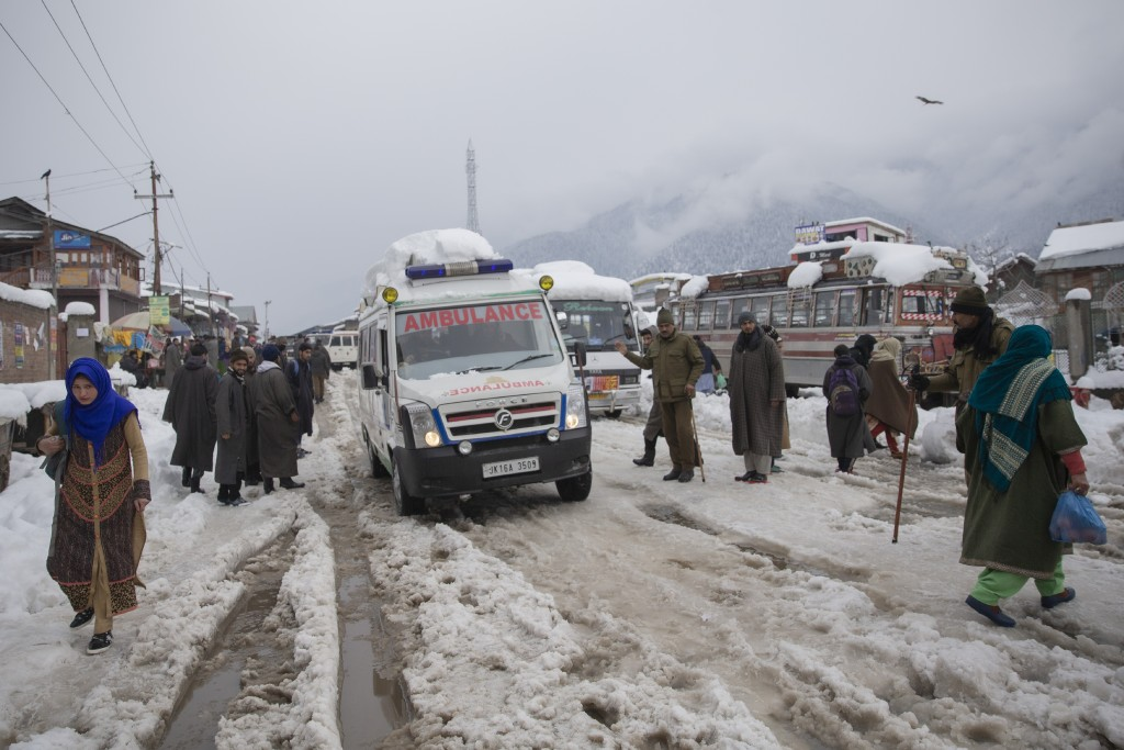 An ambulance ferries patients to a hospital through a snow covered road in Kangan, north of Srinagar, Indian controlled Kashmir, Tuesday, Jan. 14, 202...