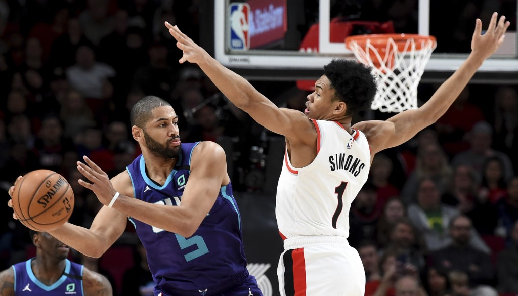 Charlotte Hornets guard Nicolas Batum, left, passes the ball around Portland Trail Blazers guard Anfernee Simons, right, during the first half of an N...