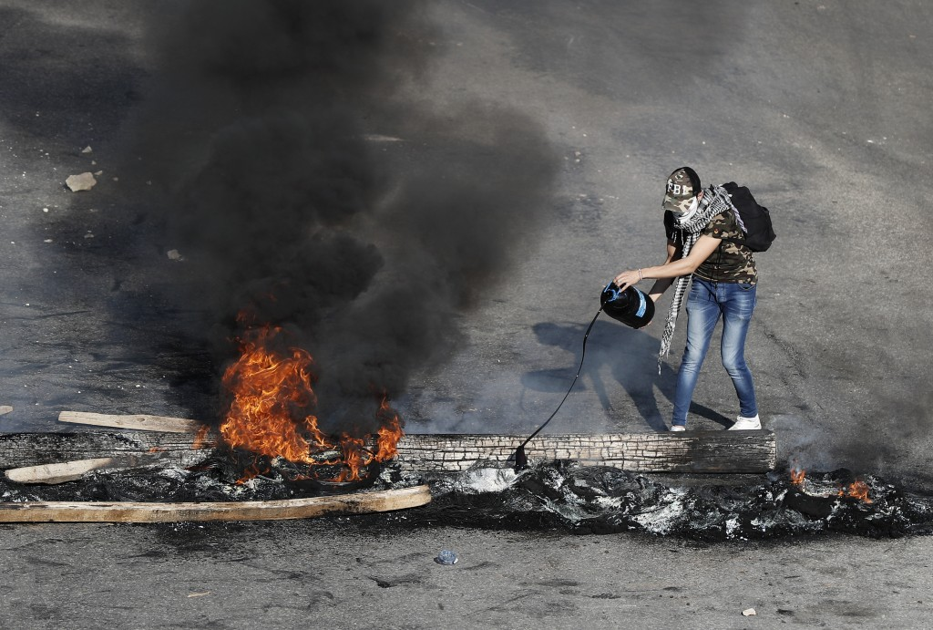 An anti-government protester drops oil on burning tires and wood during ongoing protests after weeks of calm in Beirut, Lebanon, Tuesday, Jan. 14, 202...