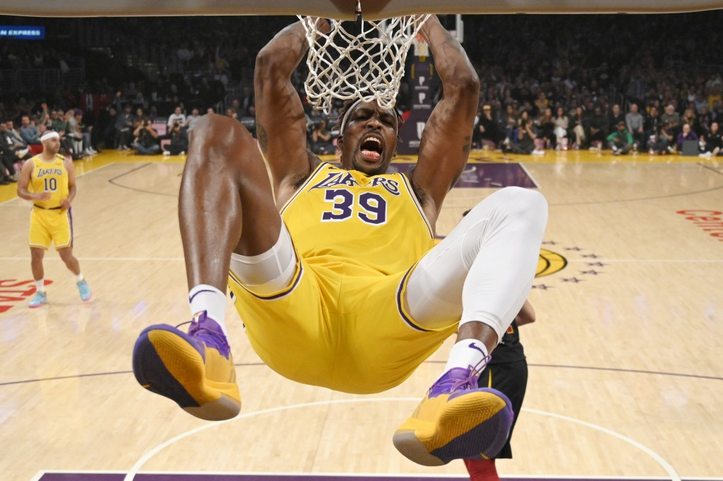 Los Angeles Lakers center Dwight Howard hangs on the basket as he dunks during the first half of an NBA basketball game against the Cleveland Cavalier...