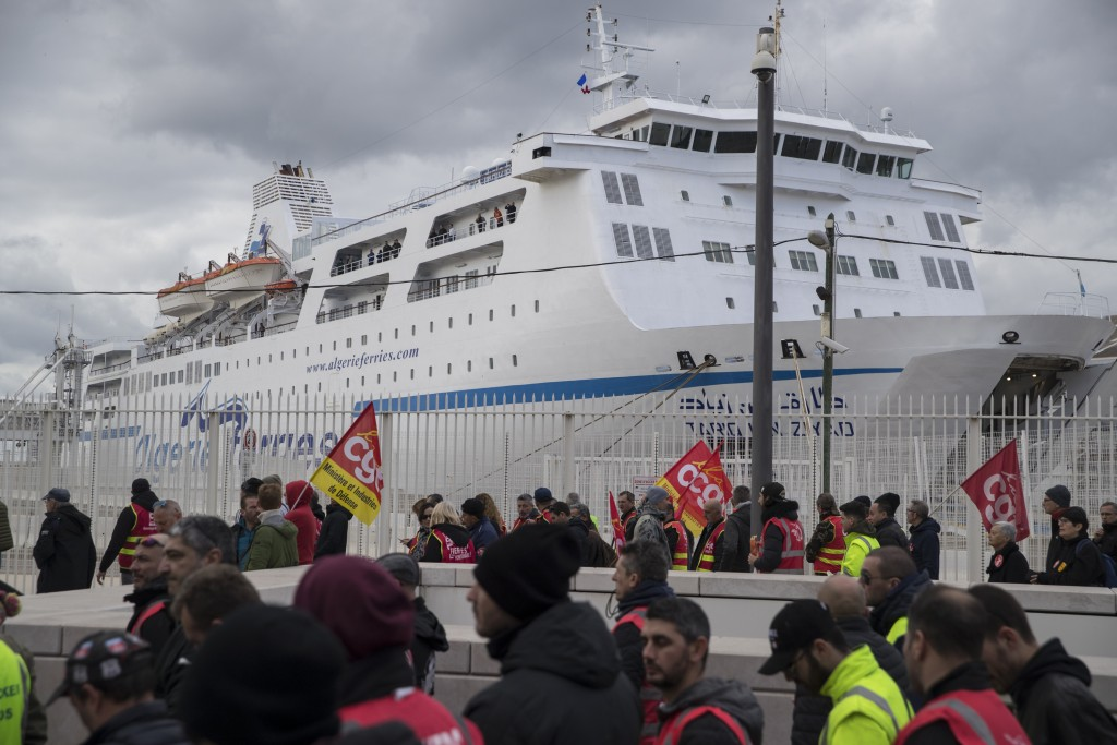 Strikers march past a ferry held at the Marseille port during a demonstration Tuesday, Jan. 14, 2020, in Marseille, southern France. Rail workers, tea...
