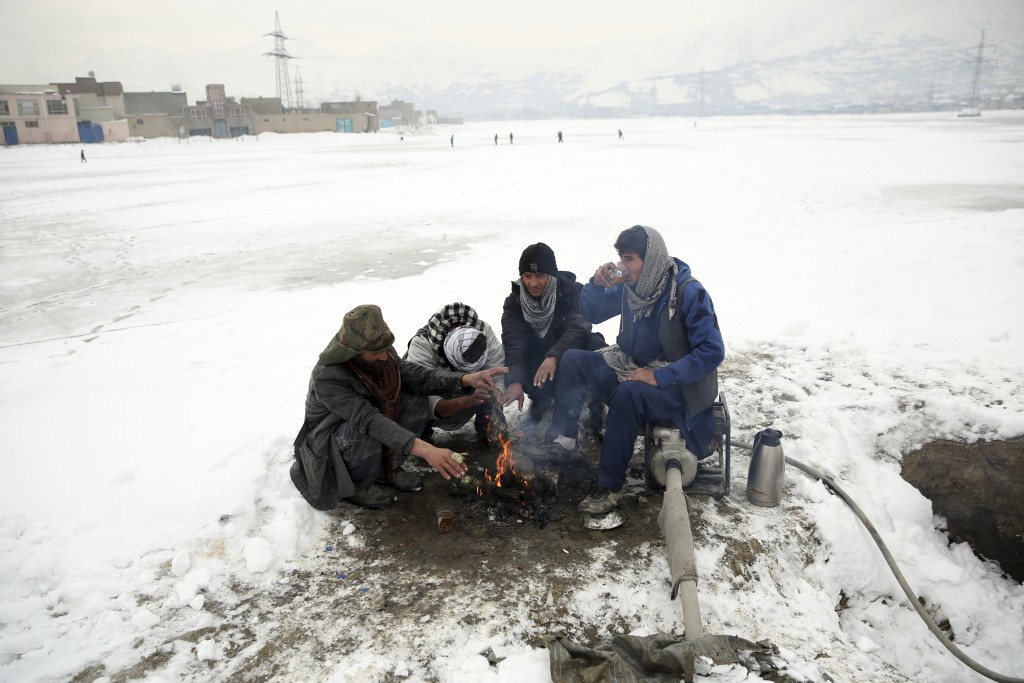 People sit around a fire to warm themselves after a heavy snowfall in Kabul, Afghanistan, Tuesday, Jan. 14, 2020. Severe winter weather has struck par...