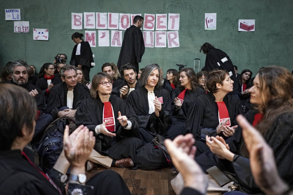Lawyers sit on the floor in the Lyon court house in Lyon, central France on Tuesday, Jan. 14, 2020, in front of posters referring to French Justice Mi...