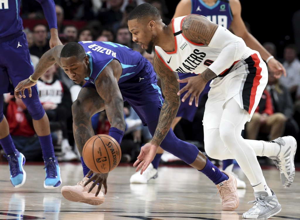 Charlotte Hornets guard Terry Rozier III, left, goes after a loose ball with Portland Trail Blazers guard Damian Lillard, right, during the first half...