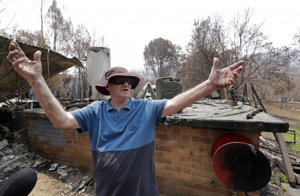 Colin Brennan stands in the debris of his destroyed house lost in the New Year's Eve wildfire at Nerrigundah, Australia, Monday, Jan. 13, 2020. The ti...