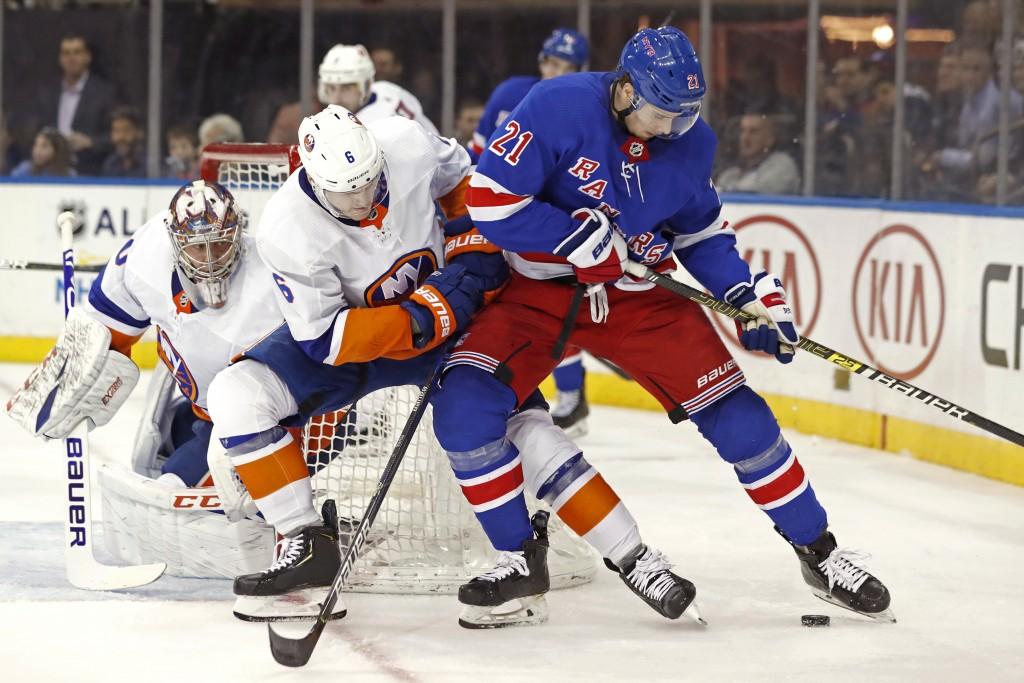 New York Islanders defenseman Ryan Pulock (6) defends New York Rangers center Brett Howden (21) in front of Islanders goaltender Semyon Varlamov (40) ...