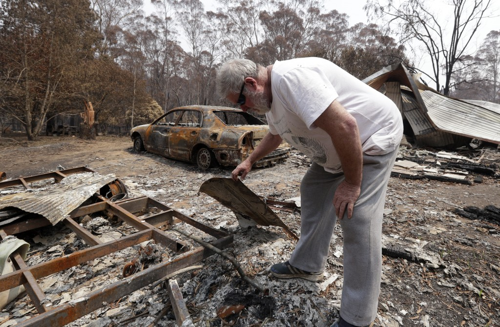 Lyle Stewart looks through burned debris at his destroyed house at Nerrigundah, Australia, Monday, Jan. 13, 2020, after a wildfire ripped through the ...