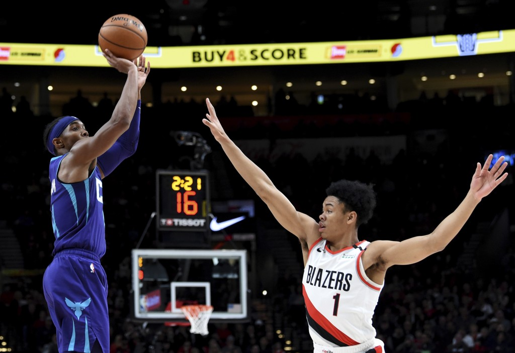 Charlotte Hornets guard Devonte' Graham, left, shoots the ball over Portland Trail Blazers guard Anfernee Simons, right, during the first half of an N...