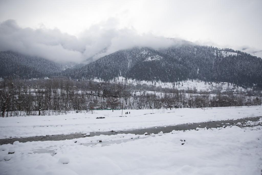 Kashmiri men walk on snow covered a field near Kangan village, north of Srinagar, Indian controlled Kashmir, Tuesday, Jan. 14, 2020. Severe winter wea...