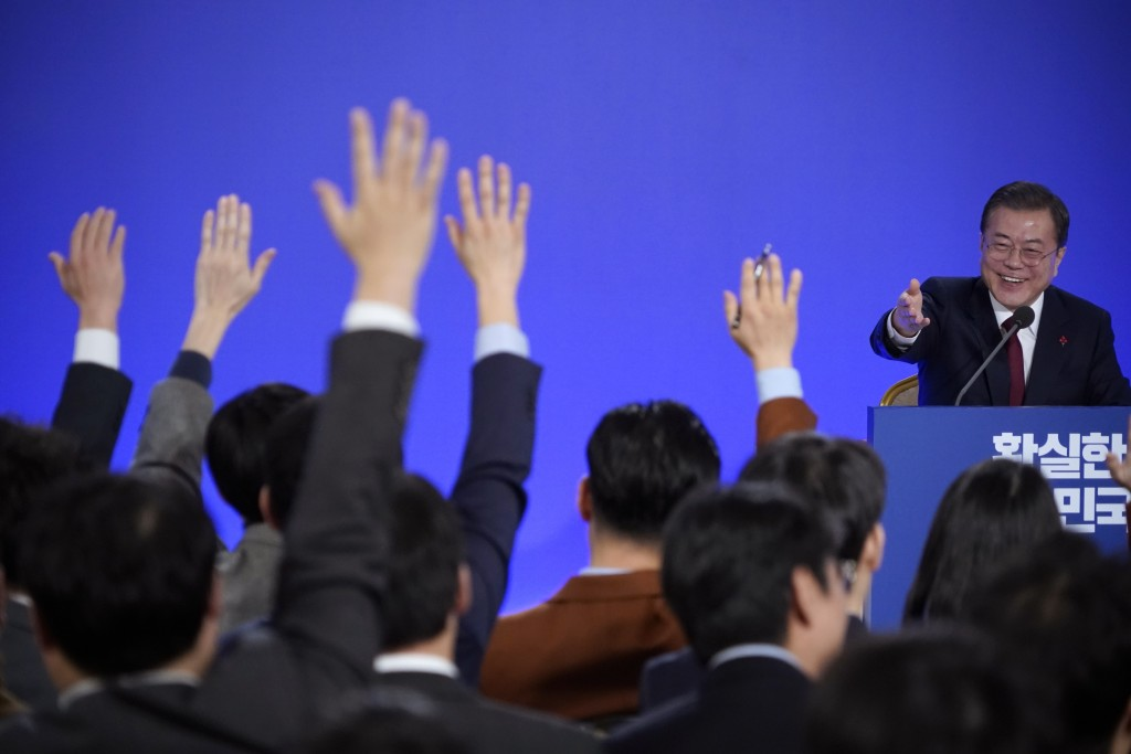 South Korean President Moon Jae-in smiles as reporters raise their hands for questions during his New Year press conference at the presidential Blue H...