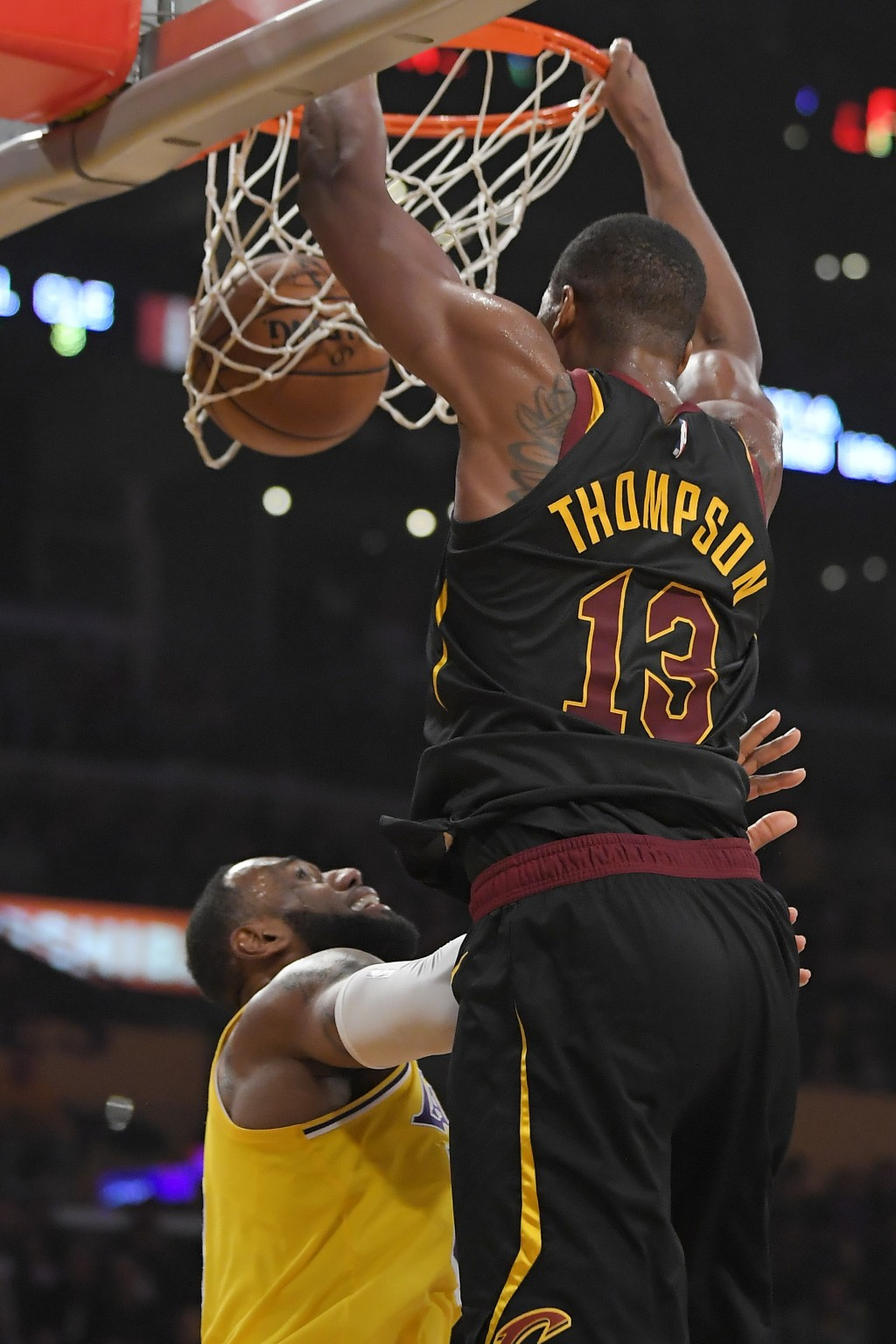 Cleveland Cavaliers center Tristan Thompson, right, dunks over Los Angeles Lakers forward LeBron James during the first half of an NBA basketball game...