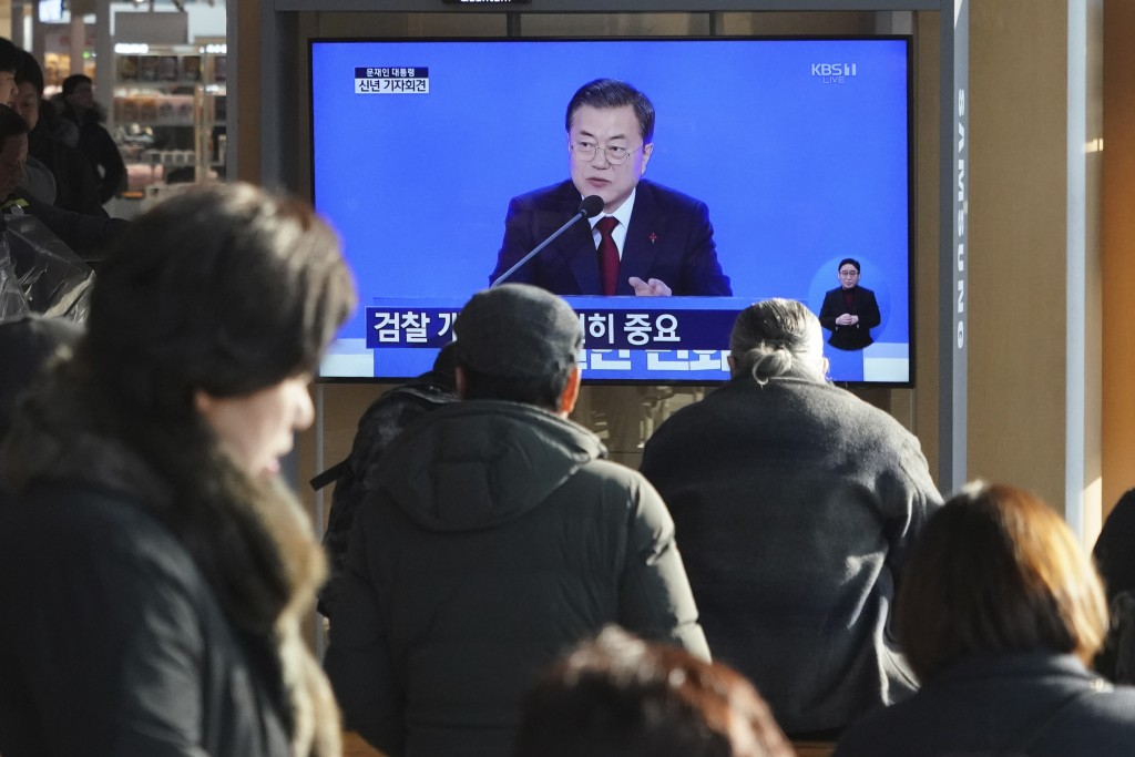 People watch a TV screen showing the live broadcast of South Korean President Moon Jae-in's New Year's press conference at the Seoul Railway Station i...