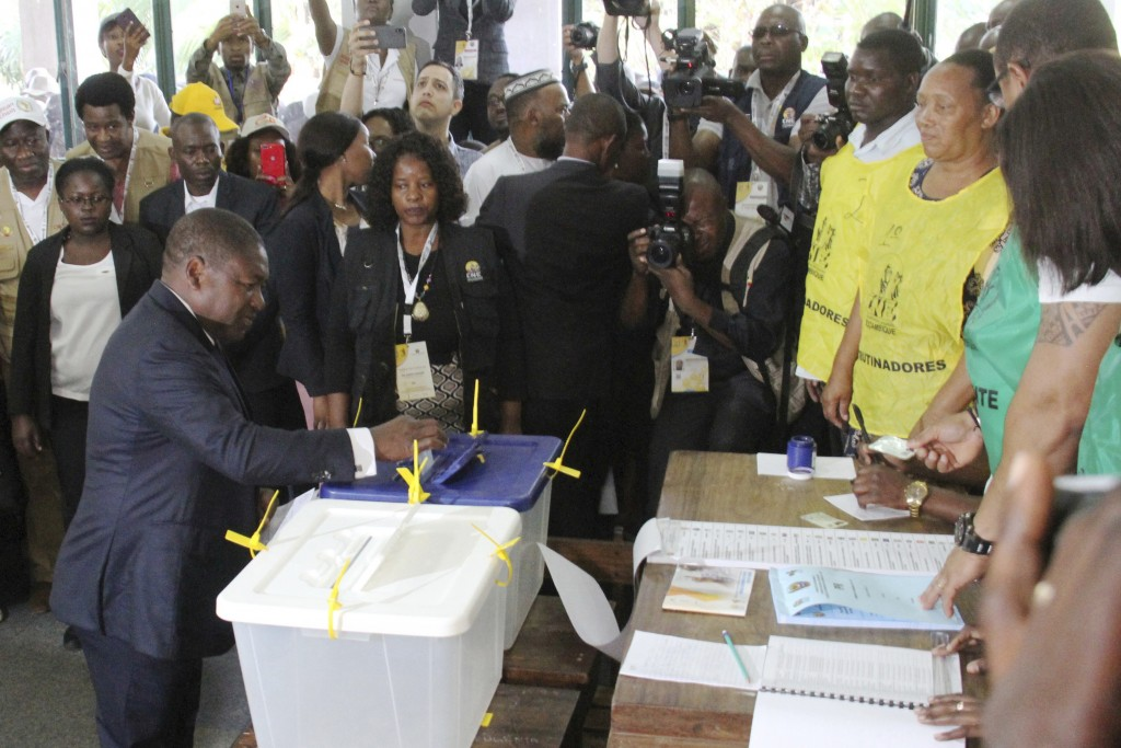 FILE - In this Tuesday, Oct. 15, 2019 file photo, Mozambican President Felipe Nyusi,left, casts his vote in Maputo in the country's elections. Nyusi i...