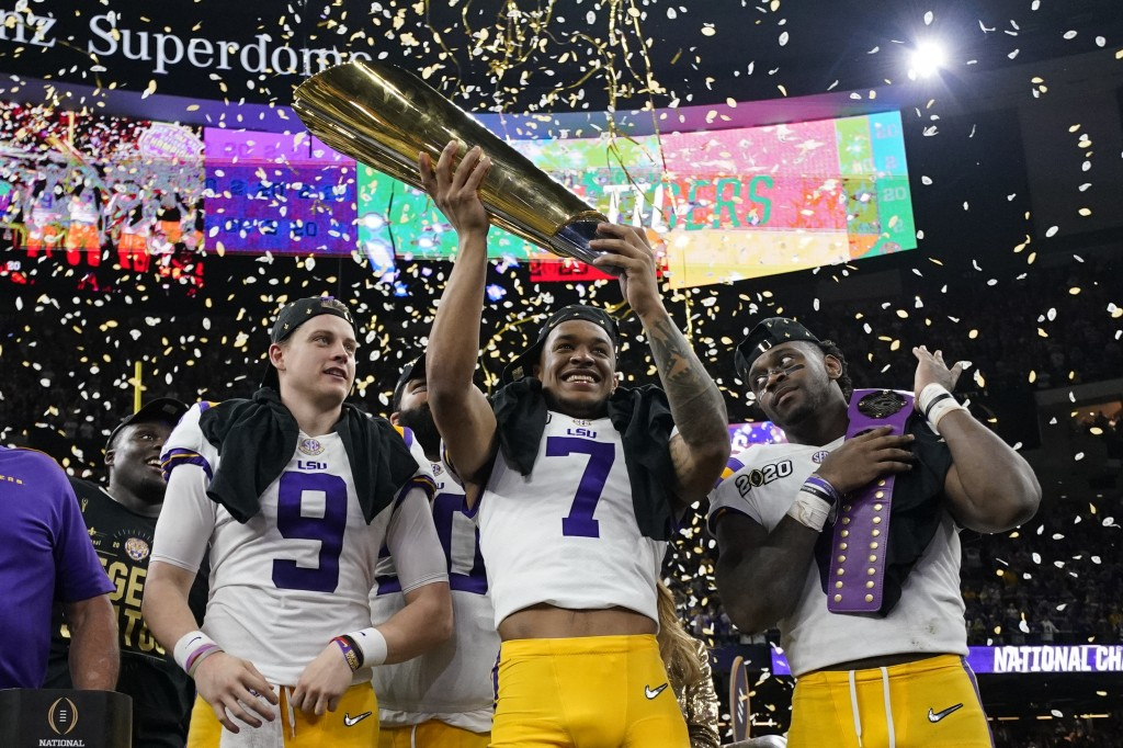 LSU safety Grant Delpit holds the trophy as quarterback Joe Burrow, left, and linebacker Patrick Queen look on after a NCAA College Football Playoff n...