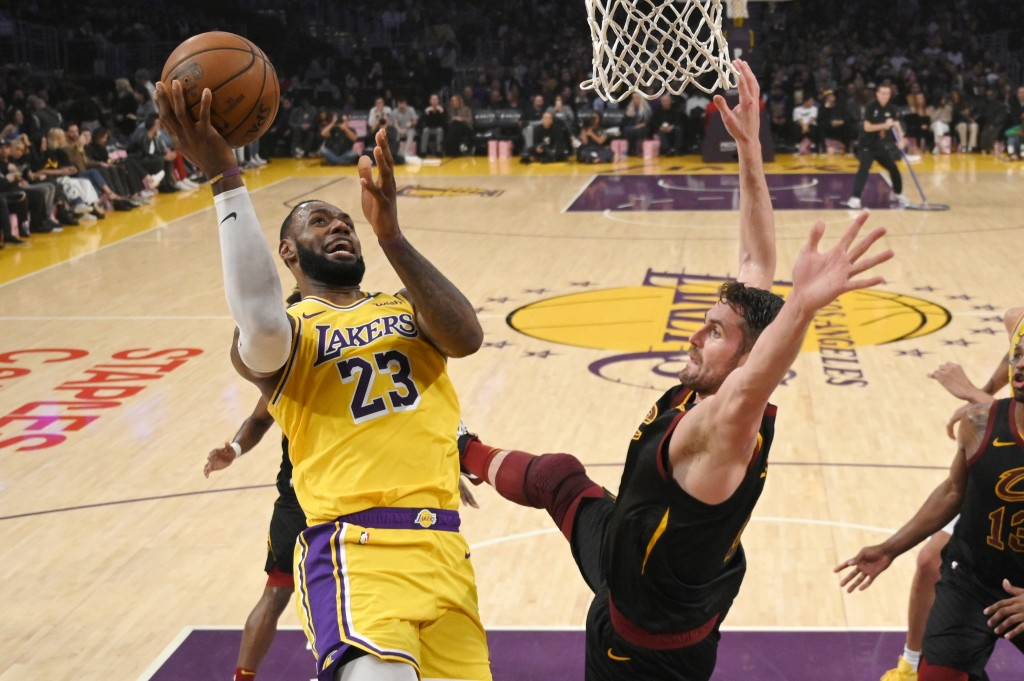 Los Angeles Lakers forward LeBron James, left, shoots as Cleveland Cavaliers forward Kevin Love defends during the first half of an NBA basketball gam...