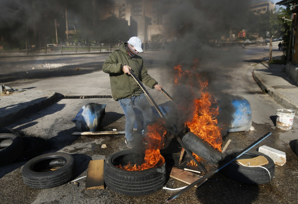 An anti-government protester burns tires the main highway during ongoing protests after weeks of calm in Beirut, Lebanon, Tuesday, Jan. 14, 2020. Leba...
