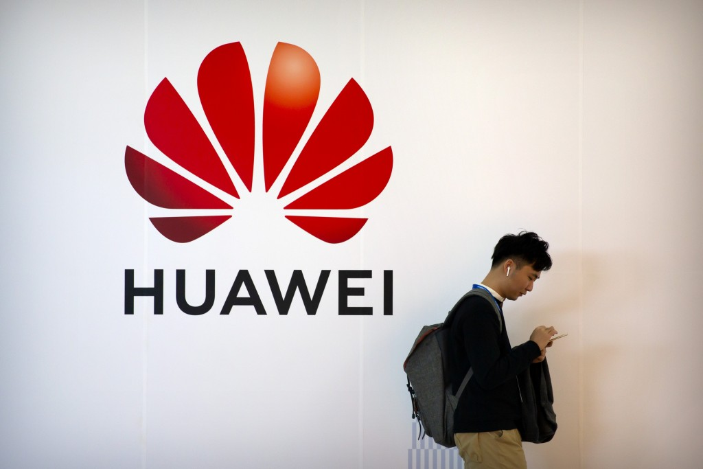 FILE - In this Oct. 31, 2019, filer photo, a man uses his smartphone as he stands near a billboard for Chinese technology firm Huawei at the PT Expo i...