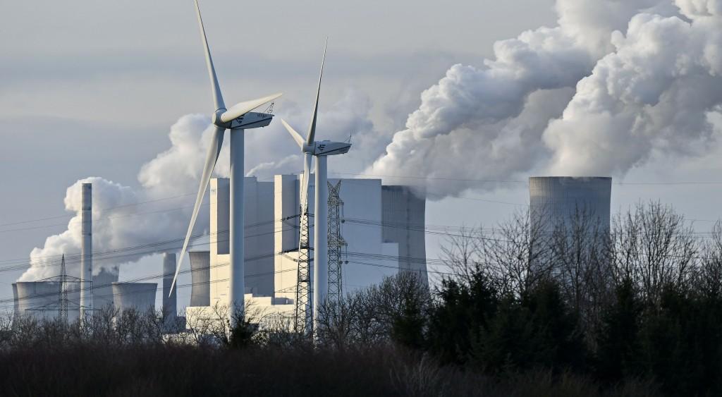 The RWE Niederaussem lignite-fired power station releases steam, behind two renewable energy producing wind turbines in Bergheim, Germany, Monday, Jan...