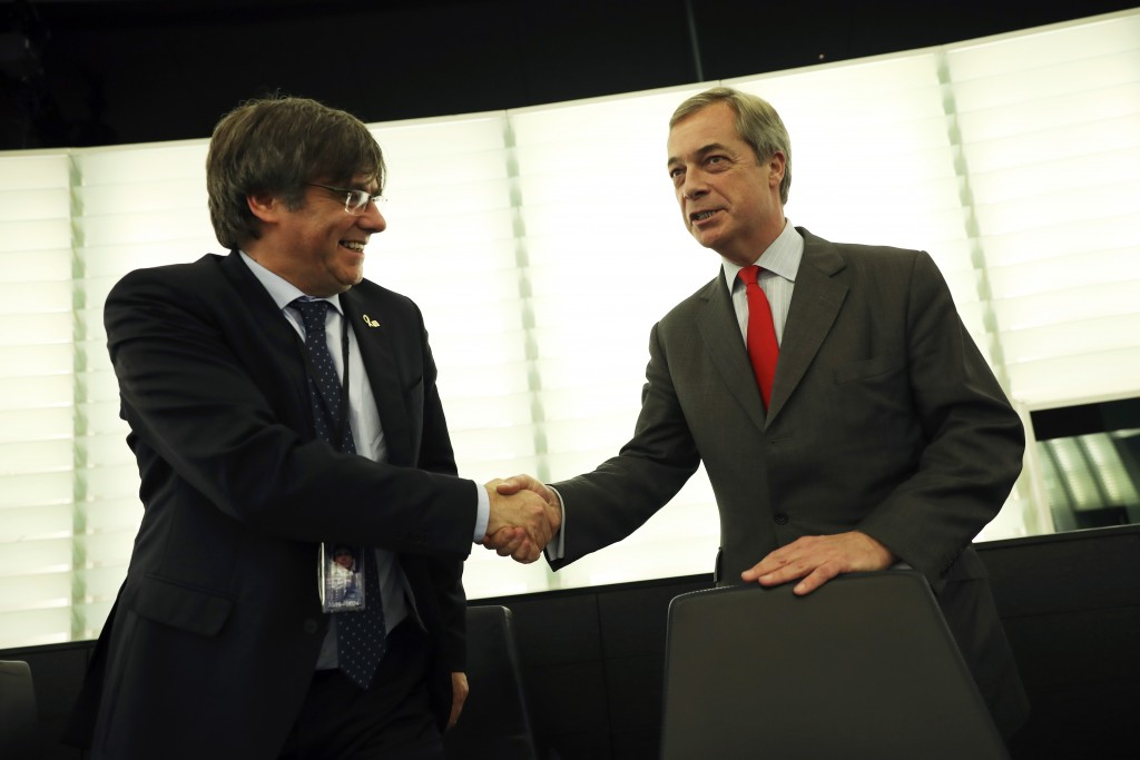 Catalonia's former regional president Carles Puigdemont, left, shakes hands with British politician Nigel Farage prior to a plenary session at the Eur...