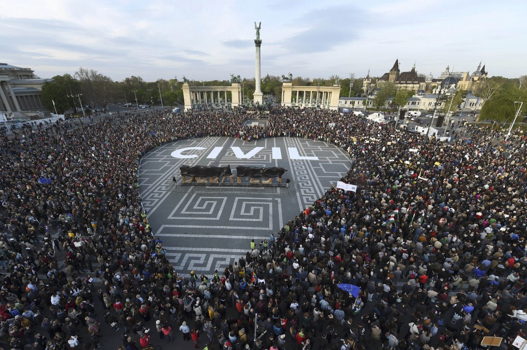 FILE - In this April 12, 2017 photo people gather to protest in Heroes Square in Budapest. Hungary's parliament has approved a law regulating civic gr...