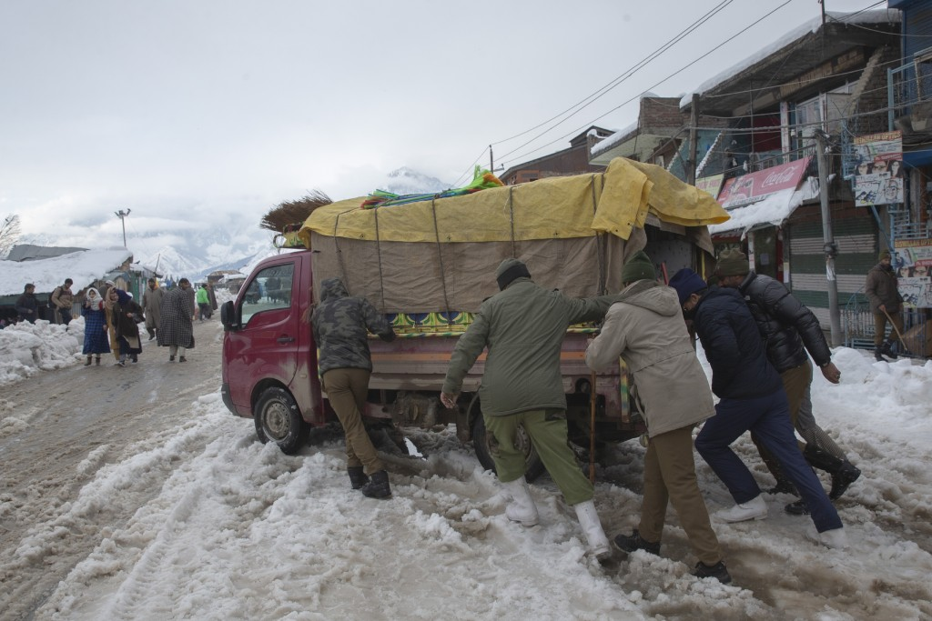 Indian police men push a load carrier stuck on a snow covered road in Kangan village, north of Srinagar, Indian controlled Kashmir, Tuesday, Jan. 14, ...