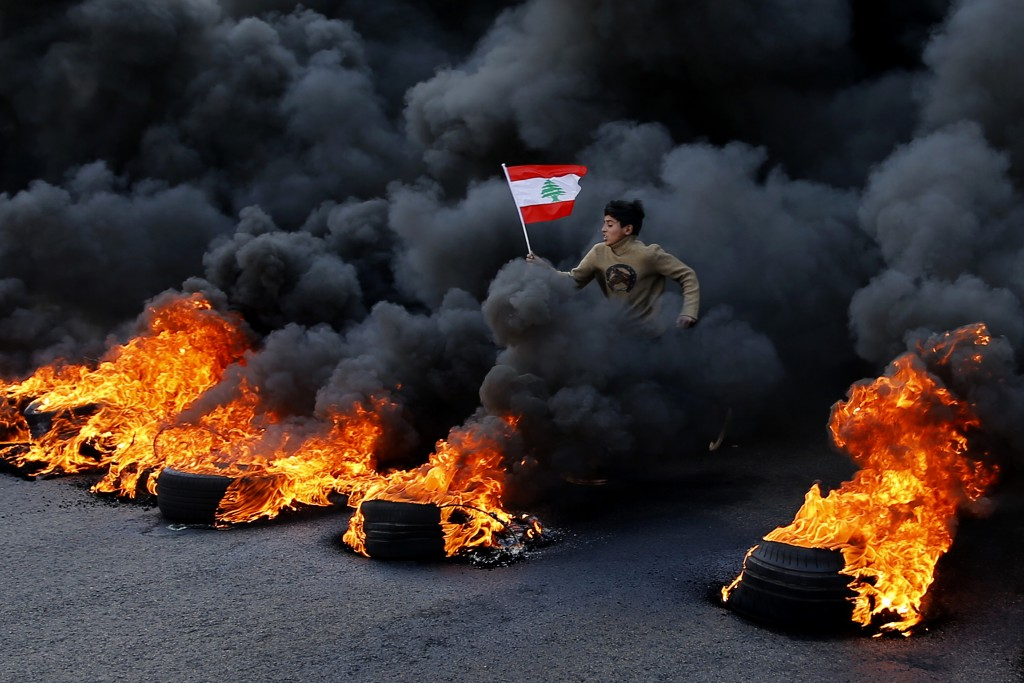 An anti-government demonstrator jumps on tires that were set on fire to block a main highway as he holds a national flag, during a protest in the town...