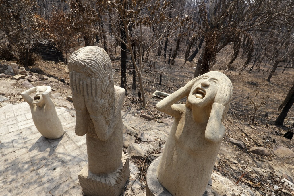 Sandstone sculptures by local fire captain Ron Threlfall show scenes of distress, Monday, Jan. 13, 2020, in Nerrigundah, Australia, that many resident...