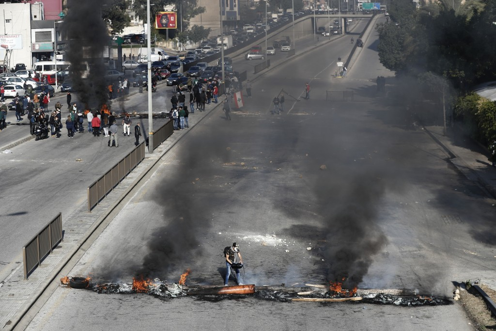 Anti-government protesters burn tires to block a main highway during ongoing protests against the government in Beirut, Lebanon, Tuesday, Jan. 14, 202...