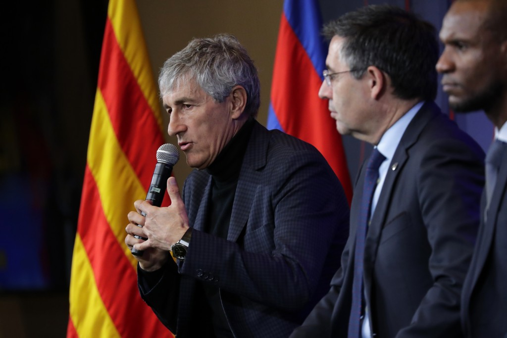 Soccer coach Quique Setien answers journalists during a news conference with FC Barcelona's President Josep Maria Bartomeu, center, and director of fo...