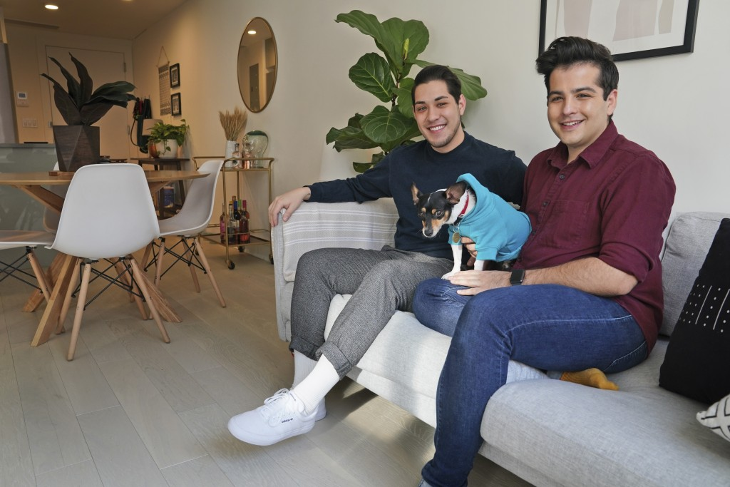 In this Monday, Nov. 25, 2019 photo, Zachariah Mohammed, left, Pete Mancilla, and their dog Remy pose for a picture in their apartment in New York. Mo...