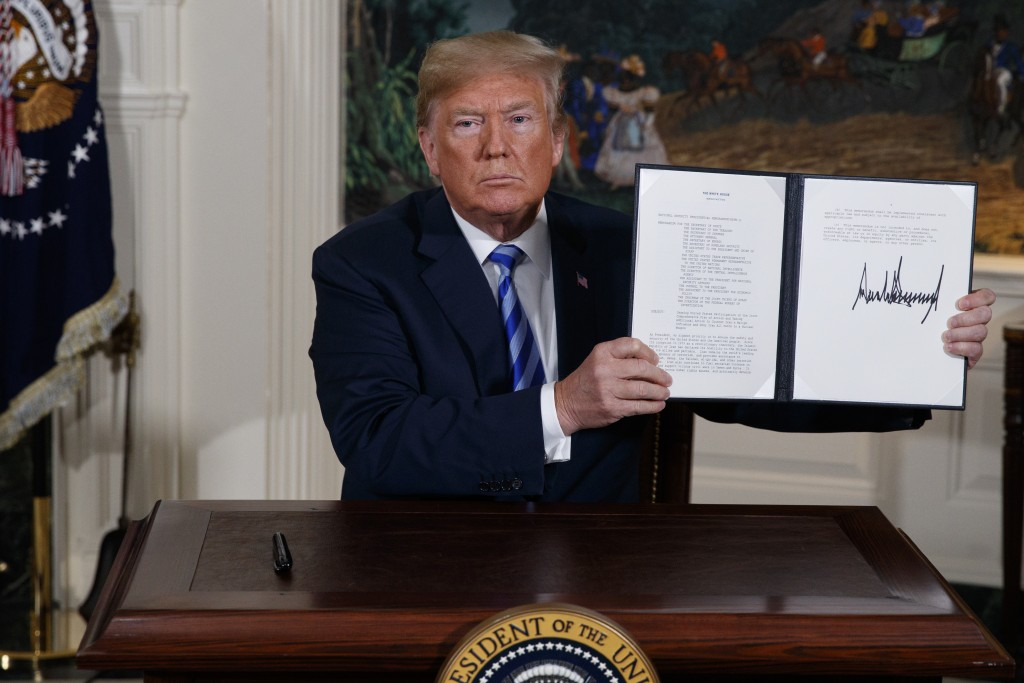 FILE - In this May 8, 2018 file photo, President Donald Trump shows a signed Presidential Memorandum after delivering a statement on the Iran nuclear ...