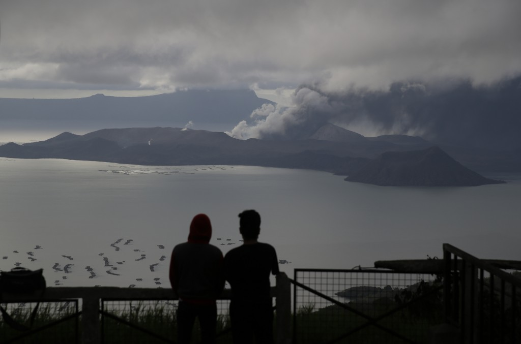 Men watch from Tagaytay, Cavite province, south of Manila, as Taal Volcano continues to spew ash on Tuesday, Jan. 14, 2020. Thousands of people fled t...