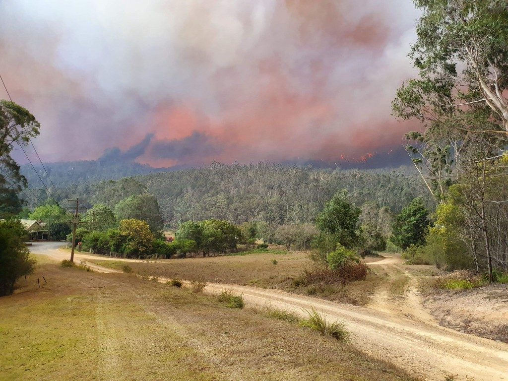 In this Dec. 30, 2019, photo provided by Siobhan Threlfall, a fire approaches the village of Nerrigundah, Australia. The tiny village has been among t...