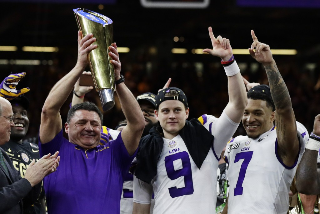 LSU head coach Ed Orgeron holds the trophy beside quarterback Joe Burrow, center, and safety Grant Delpit after a NCAA College Football Playoff nation...