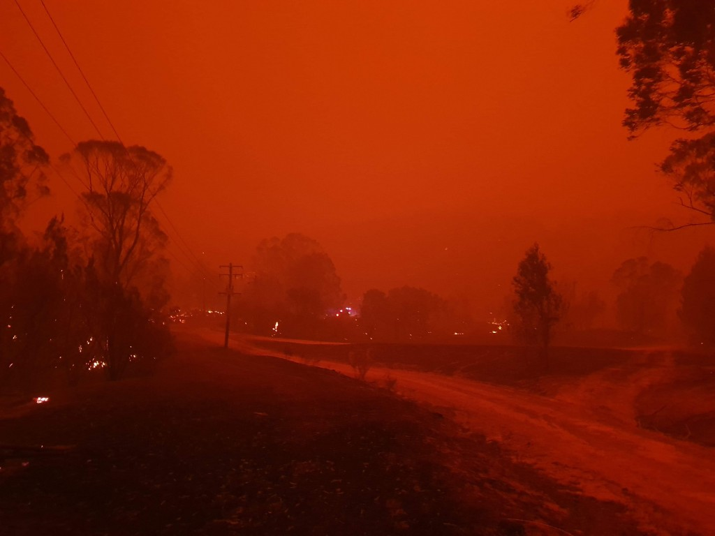 In this Dec. 31, 2019, photo provided by Siobhan Threlfall, fire and thick smoke remains the village of Nerrigundah, Australia. The tiny village has b...
