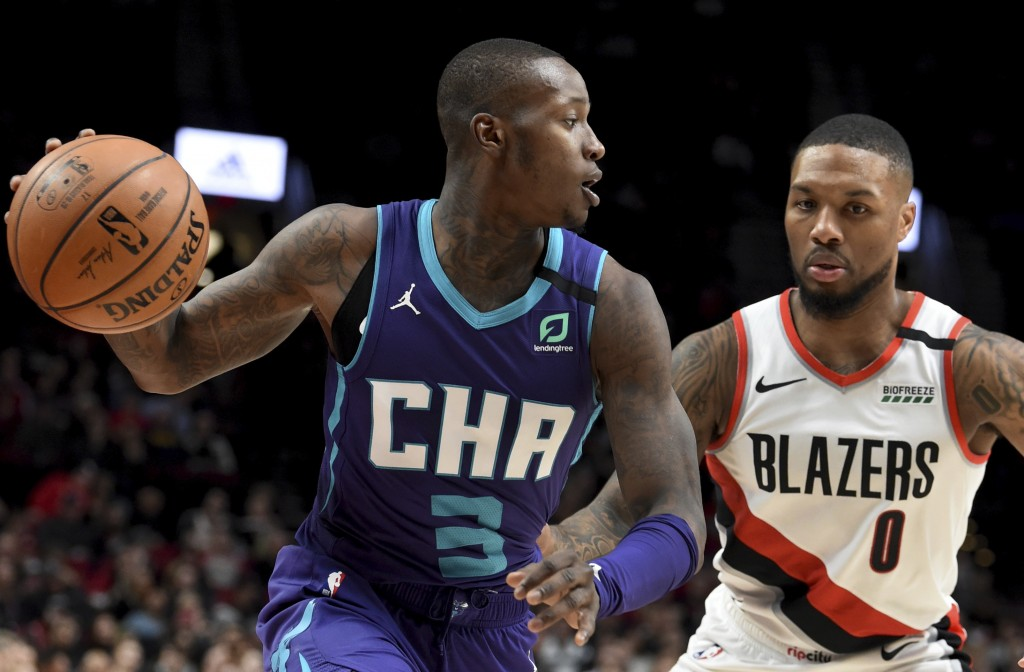 Charlotte Hornets guard Terry Rozier, left, dribbles the ball on Portland Trail Blazers guard Damian Lillard, right, during the first half of an NBA b...