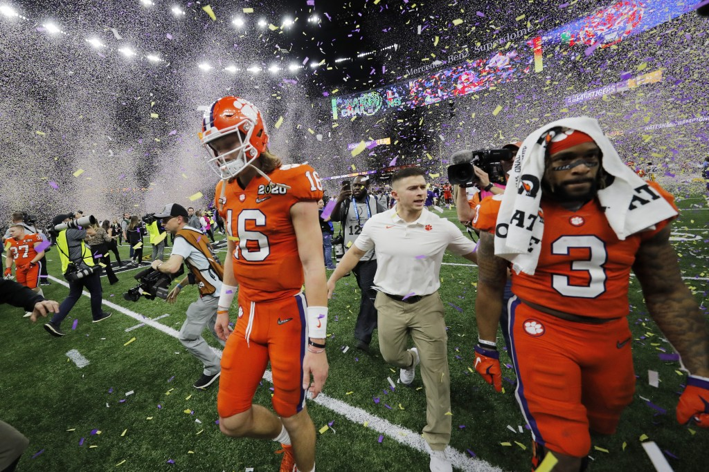 Clemson quarterback Trevor Lawrence, left, leaves the field after a NCAA College Football Playoff national championship game against LSU, Monday, Jan....