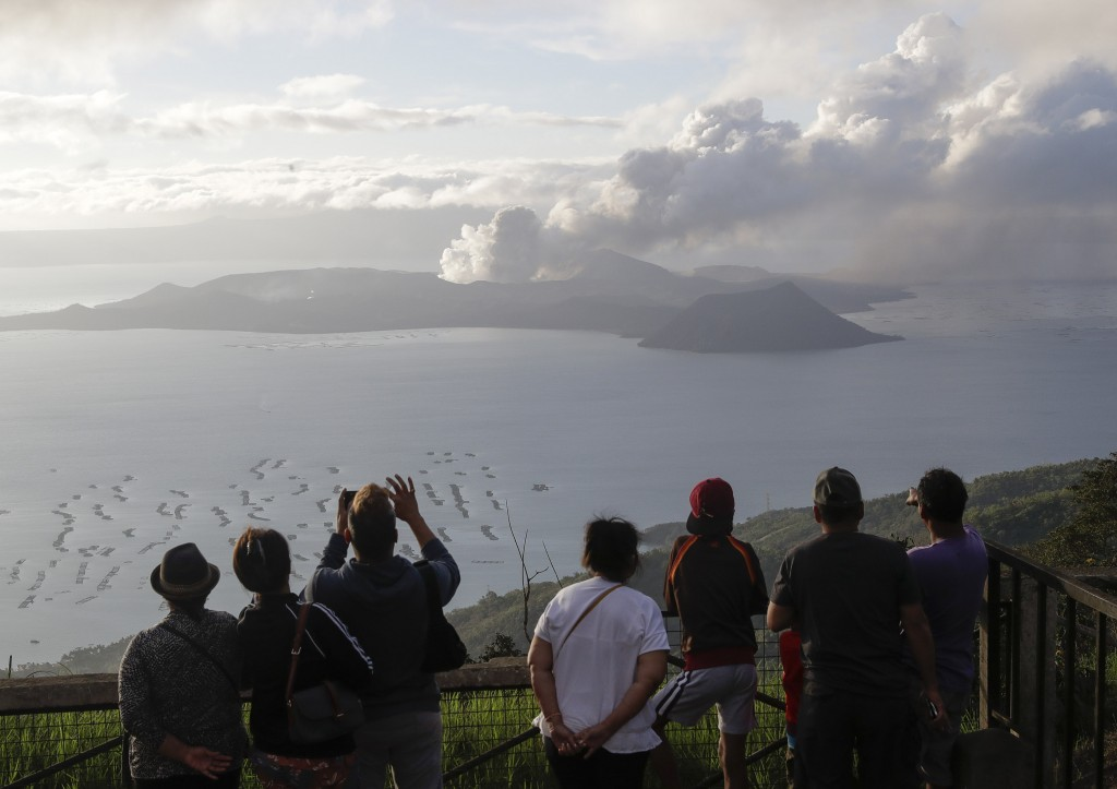 People look from Tagaytay, Cavite province, south of Manila, as Taal Volcano continues to spew ash on Tuesday, Jan. 14, 2020. Thousands of people fled...
