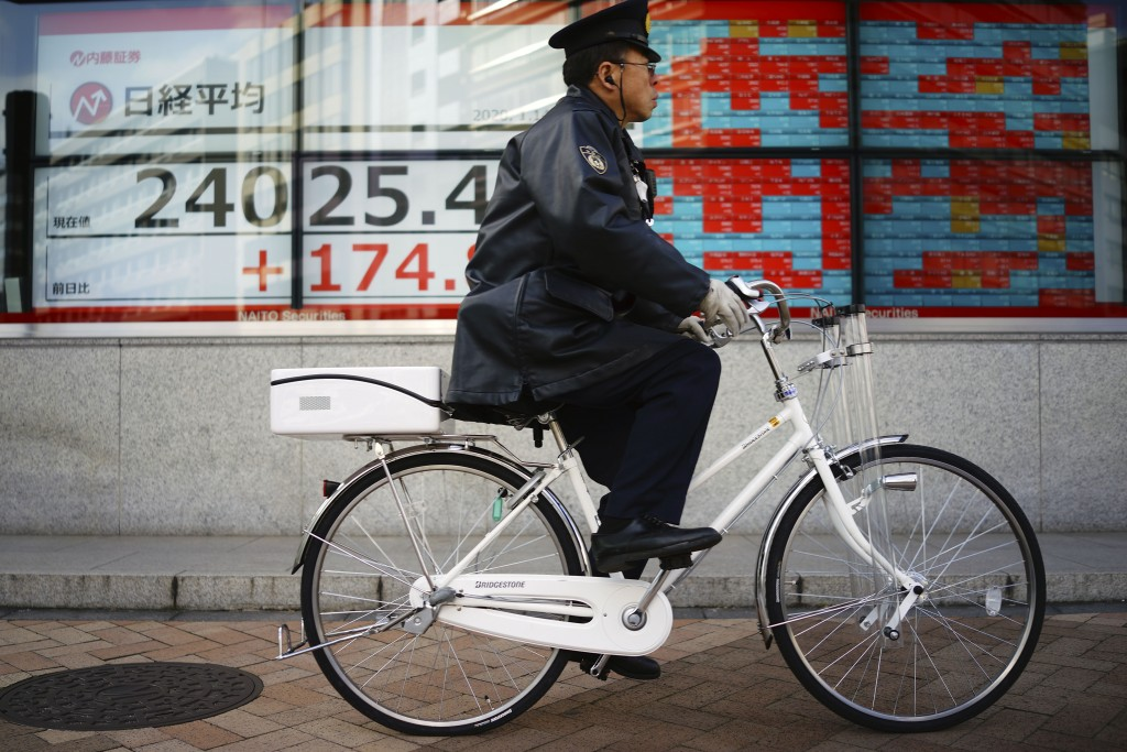 A police officer rides a bicycle past an electronic stock board showing Japan's Nikkei 225 index at a securities firm in Tokyo Tuesday, Jan. 14, 2020....