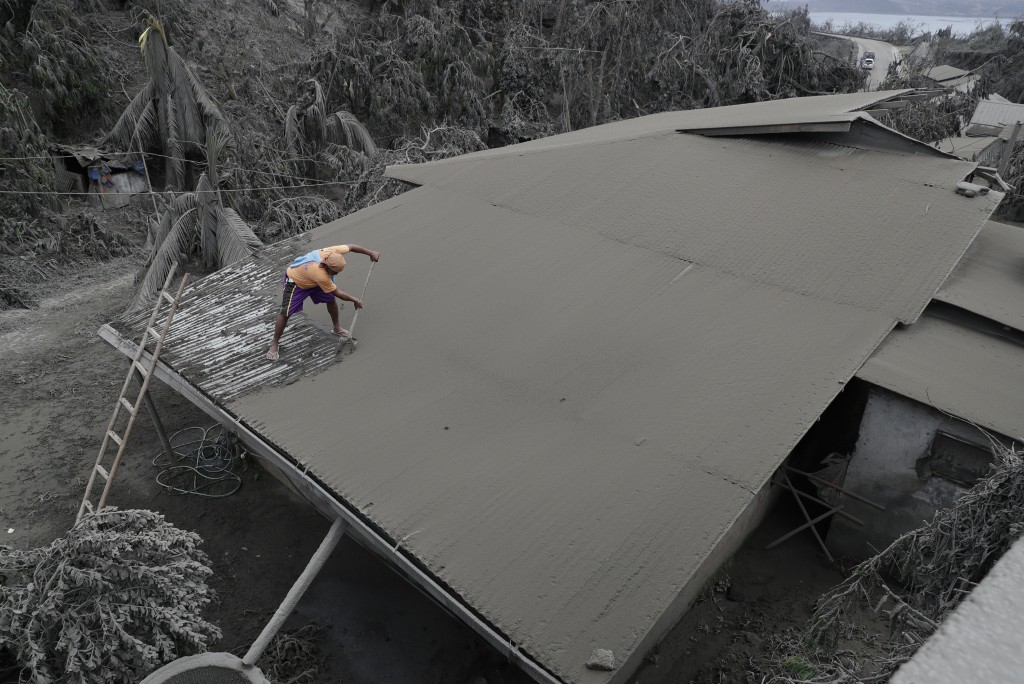 In this Tuesday, Jan. 14, 2020, photo, A resident clears volcanic ash from his roof in Laurel, Batangas province, southern Philippines on Tuesday, Jan...