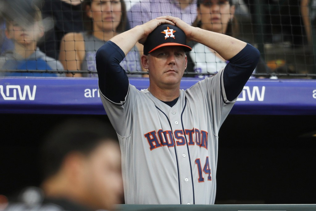 FILE - In this July 2, 2019, file photo, Houston Astros manager AJ Hinch reacts during a baseball game against the Colorado Rockies, in Denver. Housto...