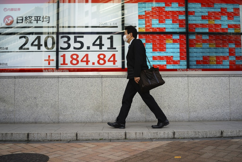 A man walks past an electronic stock board showing Japan's Nikkei 225 index at a securities firm in Tokyo Tuesday, Jan. 14, 2020. Asian shares followe...