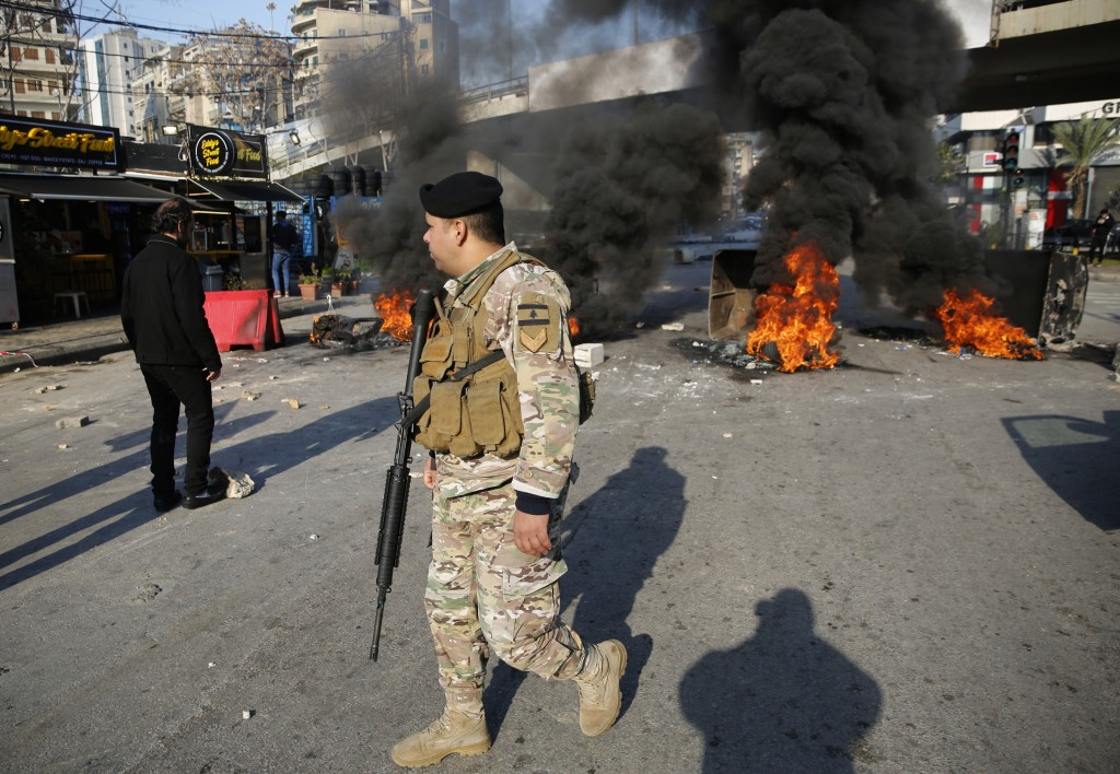 An army soldier passes burning tires during ongoing anti-government protests after weeks of calm in Beirut, Lebanon, Tuesday, Jan. 14, 2020. Lebanon i...