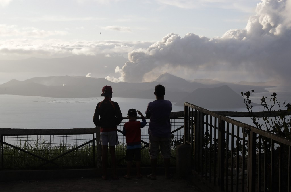 In this Tuesday, Jan. 14, 2020, photo, People watch from Tagaytay, Cavite province, south of Manila, as Taal Volcano continues to spew ash. Thousands ...